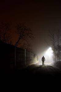 silhouette photography of man walking beside wall near street igh