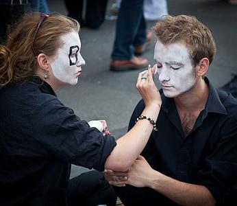 woman doing makeup on man