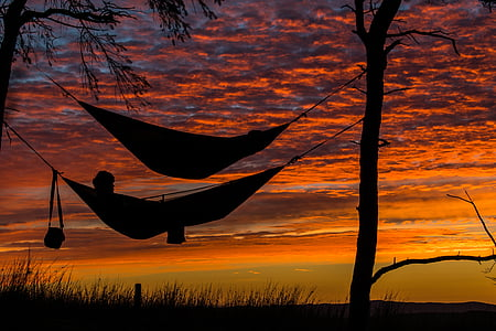 silhouette of a man on hammock during sunset