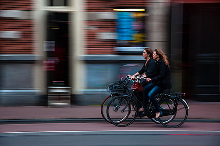 panning photography of two women cycling