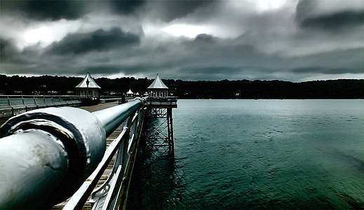 brown dock on sea under gray clouds