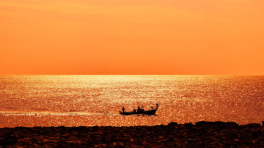 silhouette of boat during sunset