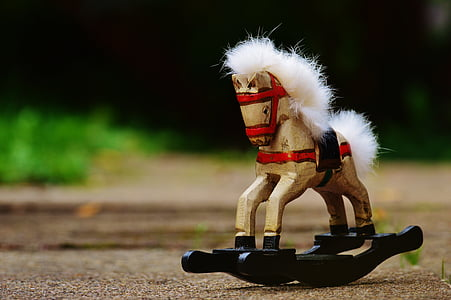 selective focus photography of brown and black toy rocking horse