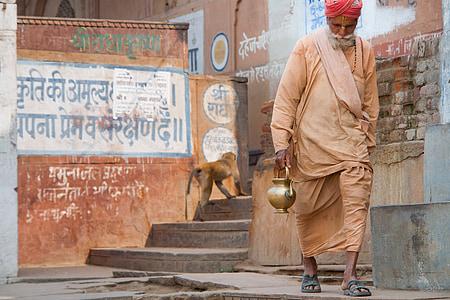 man carrying kettle walking on isle