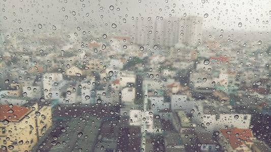 view through mirror of high rise buildings during rain