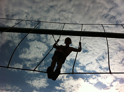 low angle photography of boy standing on hanging bridge