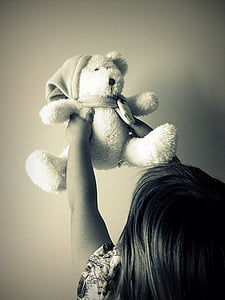 grayscale of toddler holding bear plush toy