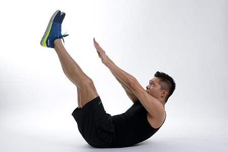 man in black shirt and black gym shorts doing ab exercise