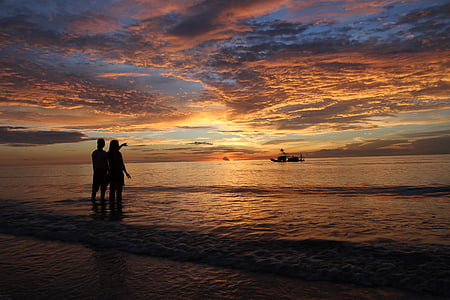 silhouette of two person near seashore during sunset