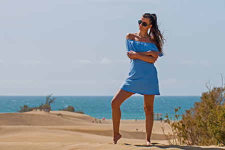 woman wearing blue off-shoulder mini dress standing near sea during daytime