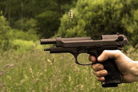 person firing black pistol near green grass field