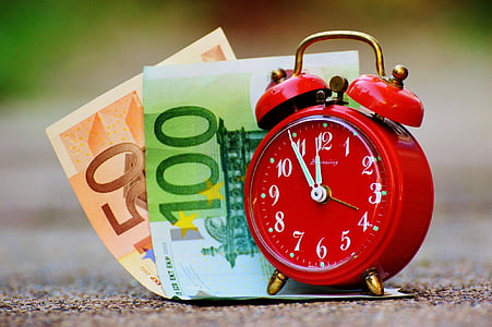 20 and 100 euro banknotes and red alarm clock with bell