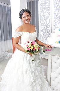 woman in white off-shoulder wedding dress holding flower bouquet