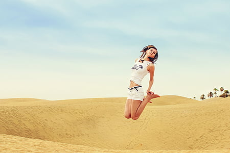 woman wearing white tank-top and white short shorts jumping on wide field during daytime