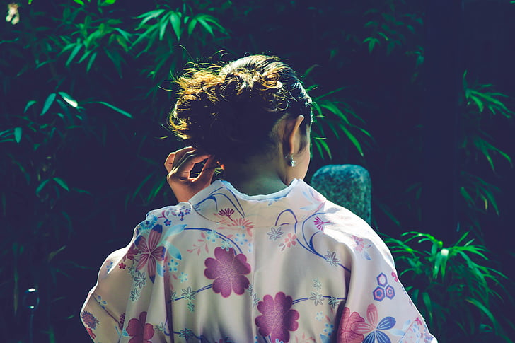 woman wearing floral top holding her ears