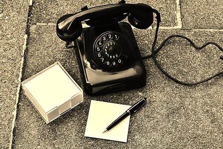 black rotary phone on black surface