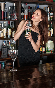 woman wearing black strapless dress holding cocktail shaker in bar