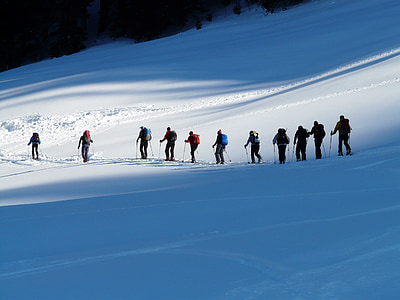 several people walking on snow mountain