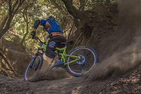 person driving full-suspension bike drift on brown soil under trees at daytime