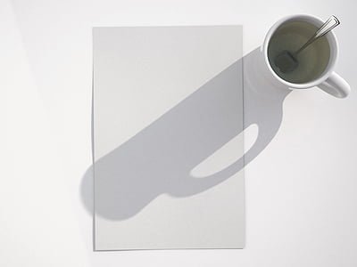 shadow of mug with tablespoon on white printer paper