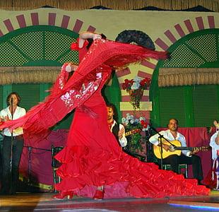 woman wearing red flare dress while dancing