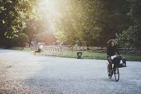 person driving bike near park bench
