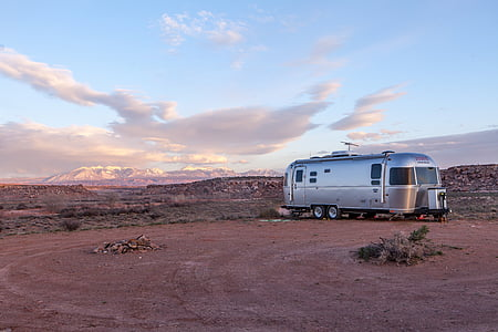gray camper trailer parked on open field at daytime