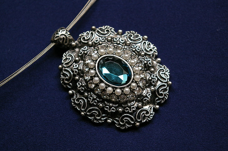 silver-colored pendant with cyan gemstone on blue velvet textile