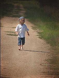 boy wearing white dress shirt and blue denim pants walking on sand during daytime