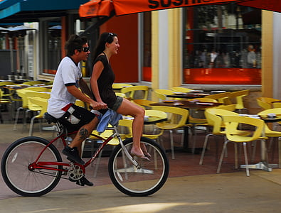 man and woman riding on bike in the city