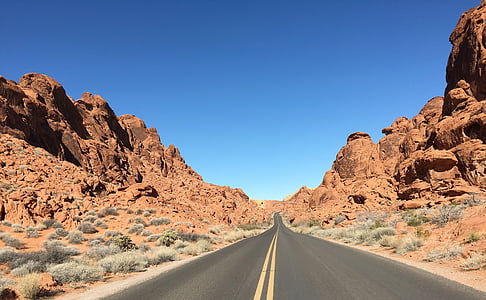 two yellow line asphalt road between brown rock cliffs during daytime