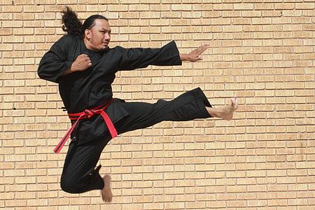 man in black karati gee doing flying kick