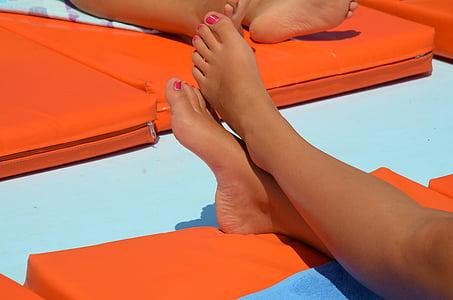 person's feet on orange fabric pad