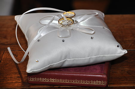 gold-colored rings on gray cushions