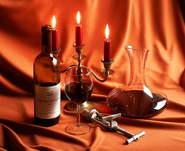 photo of wine bottle, wine glass, and candelabra