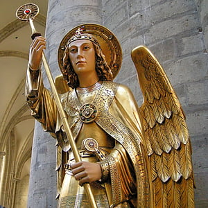 low angle of oangel wearing gold suit holding staff statue