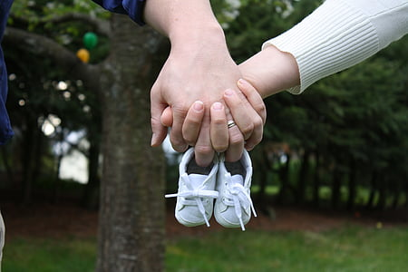 person holding pair of baby's white sneakers