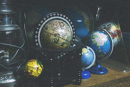 black terrestrial globe and three desk globes