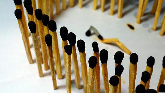 match sticks standing on white surface