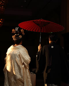 man in black traditional dress holding red umbrella