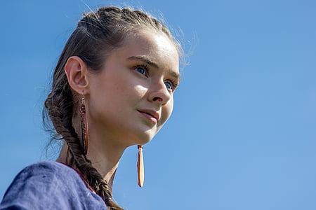 woman wearing blue top and pair of brown earrings