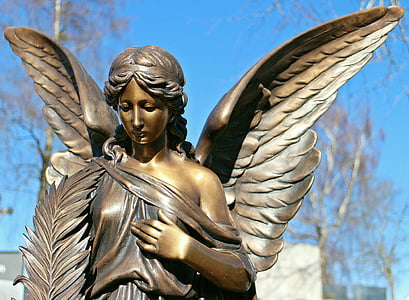brown steel angel figurine during daytime