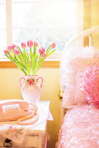 pink tulips in vase on side table