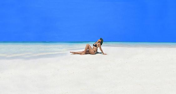 woman wearing black bikini sitting on sand near seashore with hands behind back and looking upwards