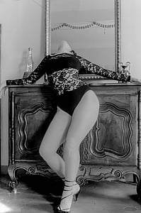 woman in lace bodysuit leaning on sideboard