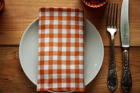 white ceramic plate beside fork and knife
