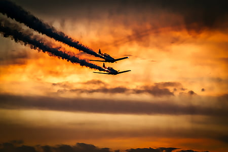 two airplanes flying in the air during sunset