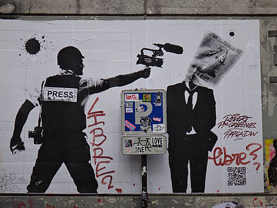 graffiti of man holding camera pointing to man in black suit jacket