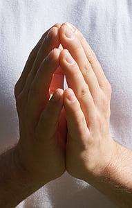 person wearing white top praying