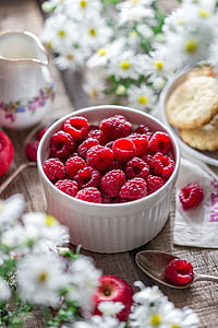selective focus photography of raspberries in white ceramic bowl